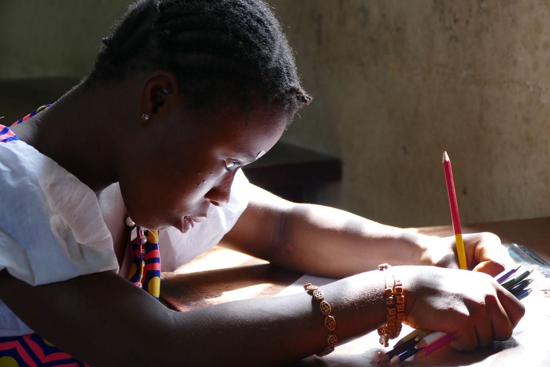 Niña escribiendo con lápices de colores - Proyecto Recomponer el corazón de Child Heroes